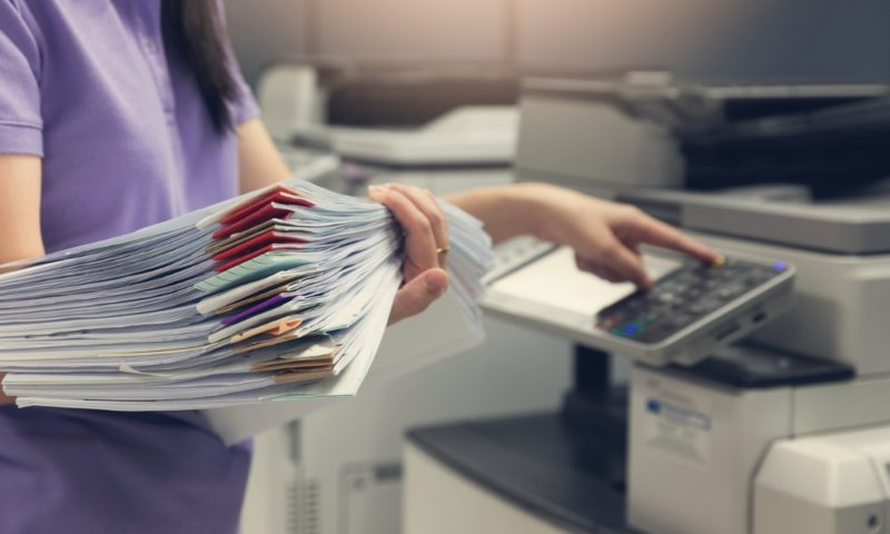 businesswoman-with-documents-using-a-printer-with-managed-print-services-mps-that-saves-money-and-costs