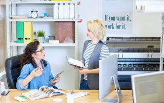 Two women converse in an office with a wide format printer in the background.